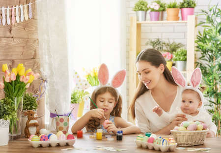 Photo for Happy easter! A mother and her daughter painting Easter eggs. Happy family preparing for Easter. Cute little child girl wearing bunny ears on Easter day. - Royalty Free Image