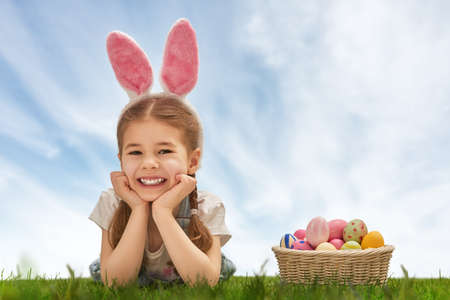 Photo for Cute little child girl wearing bunny ears on Easter day. Girl hunts for Easter eggs on the lawn. Girl has basket with painted eggs. - Royalty Free Image