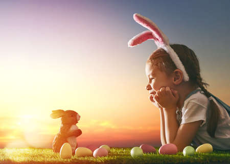 Photo for Cute little child girl wearing bunny ears on Easter day. Girl hunts for Easter eggs on the lawn. Girl with Easter eggs and bunny in the rays of the setting sun. - Royalty Free Image
