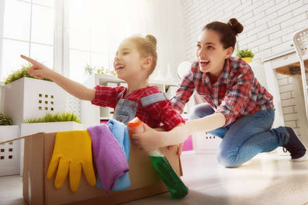 Photo pour Happy family cleans the room. Mother and daughter do the cleaning in the house. A young woman and a little child girl having fun and riding in cardboard boxes at home. - image libre de droit