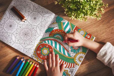 Photo pour Child paint a coloring book. New stress relieving trend. Concept mindfulness, relaxation. - image libre de droit