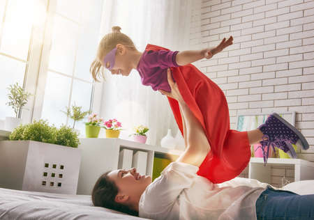 Foto de Mother and her child girl playing together. Girl in an costume. The child having fun and jumping on the bed. - Imagen libre de derechos