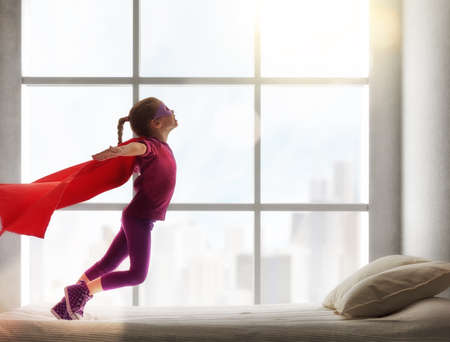 Photo pour Child girl in an  costume plays. The child having fun and jumping on the bed. - image libre de droit