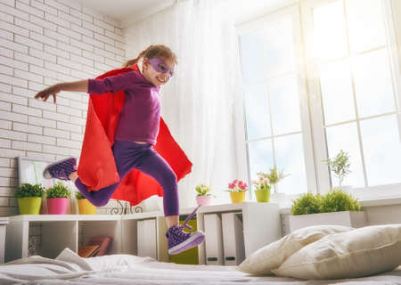 Foto de Child girl in an  costume plays. The child having fun and jumping on the bed. - Imagen libre de derechos