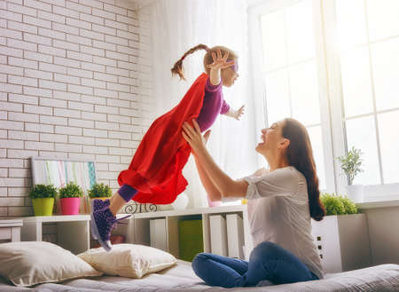 Photo pour Mother and her child girl playing together. Girl in an  costume. The child having fun and jumping on the bed. - image libre de droit
