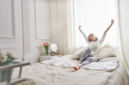 Photo pour Happy young woman enjoying sunny morning on the bed - image libre de droit
