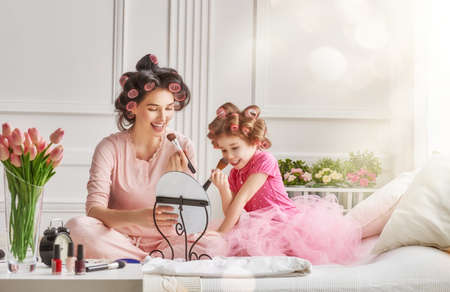 Photo pour Happy loving family. Mother and daughter are doing hair and having fun. Mother and daughter doing your makeup sitting on the bed in the bedroom. - image libre de droit