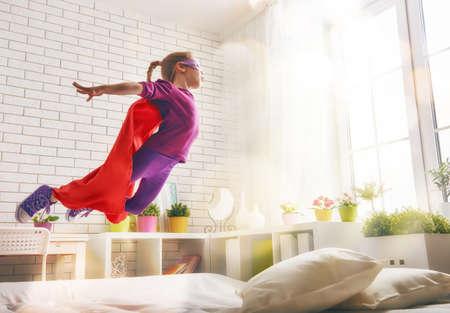 Foto de Child girl in Superhero's costume plays. The child having fun and jumping on the bed. - Imagen libre de derechos