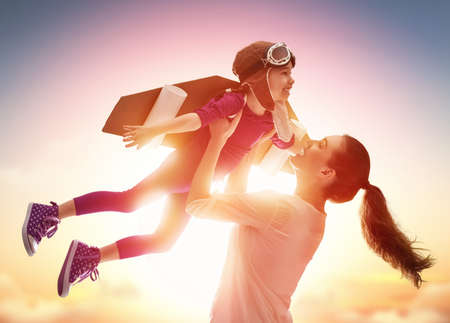 Photo pour Mother and her child playing together. Little child girl plays astronaut. Child in an astronaut costume plays and dreams of becoming a spaceman. Happy loving family having fun. - image libre de droit