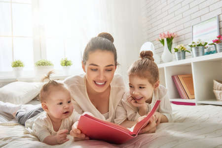 Photo pour happy loving family. pretty young mother reading a book to her daughters - image libre de droit