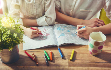 Foto de Child and adult  are painting a coloring book. New stress relieving trend. Concept mindfulness, relaxation. - Imagen libre de derechos
