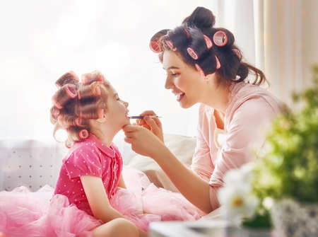 Photo for Happy loving family. Mother and daughter are doing hair and having fun. Mother putting lipstick on her daughter. - Royalty Free Image