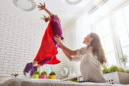 Foto de Mother and her child girl playing together. Girl in an Superhero's costume. The child having fun and jumping on the bed. - Imagen libre de derechos