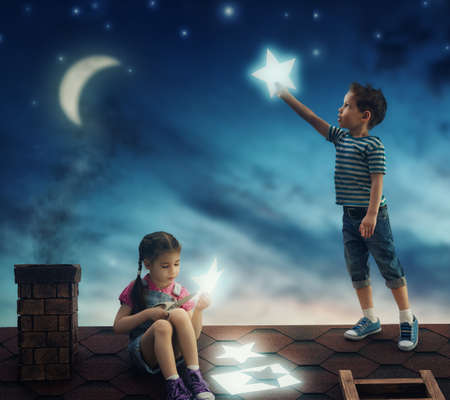 Foto de Fairy tale! The children hung the stars in the sky. Boy and girl on the roof cut out stars. - Imagen libre de derechos