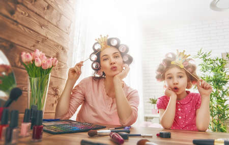 Photo pour Happy loving family. Mother and daughter are doing hair, manicures, doing your makeup and having fun. Mother and daughter sitting at dressing table at house. - image libre de droit