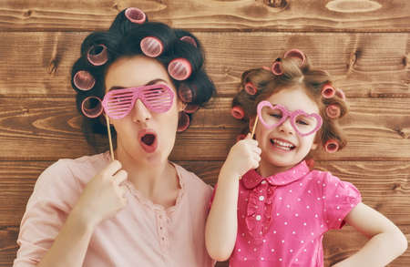 Photo for Funny family! Mother and her child daughter girl with a paper accessories. Beauty funny girl holding paper glasses on stick. Beautiful young woman holding paper glasses on stick. - Royalty Free Image