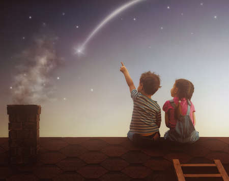 Foto de Two cute children sit on the roof and look at the stars. Boy and girl make a wish by seeing a shooting star. - Imagen libre de derechos
