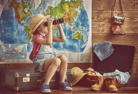 Foto de happy baby girl getting ready for the journey. Girl packs her bags and playing with binoculars. - Imagen libre de derechos