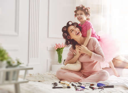 Foto de Happy loving family. Mother and daughter are doing hair and having fun. Mother and her child girl playing and hugging. - Imagen libre de derechos