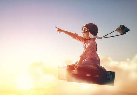 Foto de Dreams of travel! Child flying on a suitcase against the backdrop of a sunset. - Imagen libre de derechos