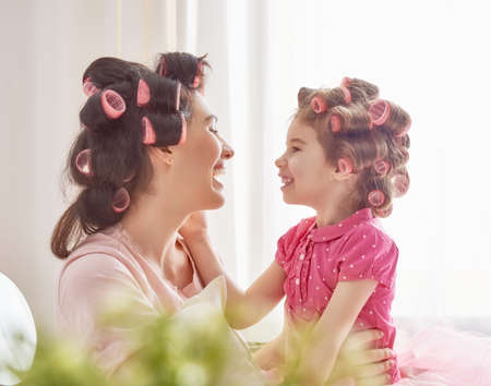 Photo pour Happy loving family. Mother and daughter are doing hair and having fun. Mother and her child girl playing and hugging. - image libre de droit