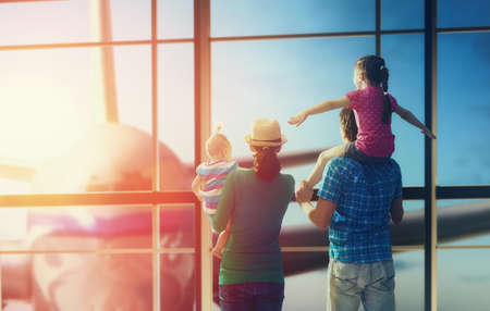 Foto de Happy family with children at the airport. Parents and their children look out the window at the plane. - Imagen libre de derechos