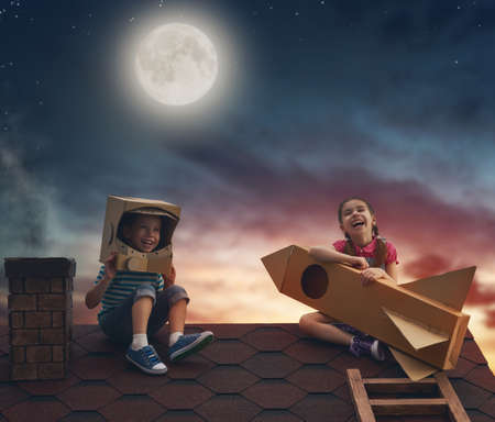 Foto de Two little children playing astronauts. Children on the background of moon sky. Child boy in an astronaut costume and child girl with toy rocket standing on the roof of the house and looking at the sky and dreaming of becoming a spacemen. - Imagen libre de derechos
