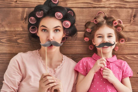 Photo pour Funny family! Mother and her child daughter girl with a paper accessories. Beauty funny girl holding paper mustache on stick. Beautiful young woman holding paper mustache on stick. - image libre de droit