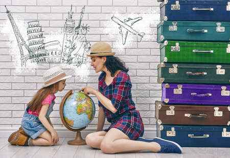 Foto de happy family preparing for the journey. mother and daughter looking at a globe and choose a country to travel. - Imagen libre de derechos