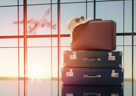 Foto de the concept of travel and holiday. suitcases against the window and the sunsets - Imagen libre de derechos
