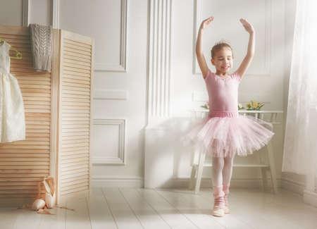 Foto de Cute little girl dreams of becoming a ballerina. Child girl in a pink tutu dancing in a room. Baby girl is studying ballet. - Imagen libre de derechos