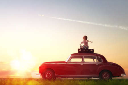 Photo pour Toward adventure! Girl relaxing and enjoying road trip. Happy child girl sitting on roof of vintage car. - image libre de droit