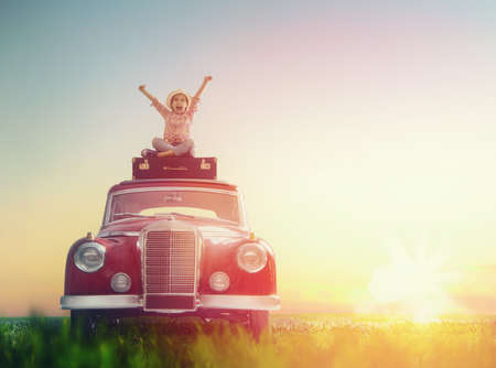 Foto de Toward adventure! Girl relaxing and enjoying road trip. Happy child girl sitting on roof of vintage car. - Imagen libre de derechos