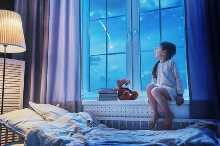 Photo pour Cute child girl sitting at the window and looking at the stars. Girl making a wish by seeing a shooting star at bedtime night. - image libre de droit