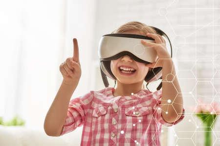 Foto de Cute little child girl playing game in virtual reality glasses. - Imagen libre de derechos