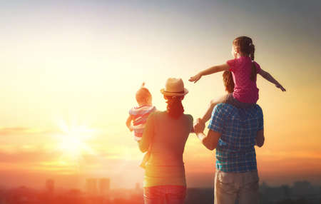 Foto de happy family at sunset. father, mother and two children daughters having fun and playing in nature. the child sits on the shoulders of his father. - Imagen libre de derechos