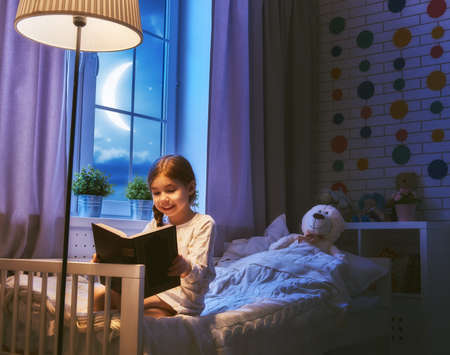 Photo for Cute little child girl reading a book under a lamp. Kid girl sitting in her bed on a dark moonlit night. - Royalty Free Image