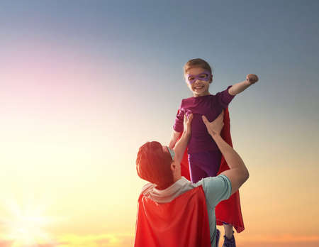 Foto de Happy loving family. Father and his daughter child girl playing outdoors. Daddy and her child girl in an Superhero's costumes. Concept of Father's day. - Imagen libre de derechos