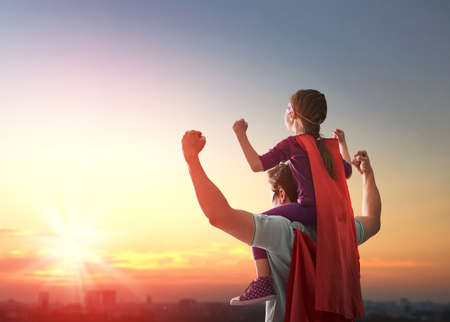 Photo pour Happy loving family. Father and his daughter child girl playing outdoors. Daddy and his child girl in an Superhero's costumes. Concept of Father's day. - image libre de droit