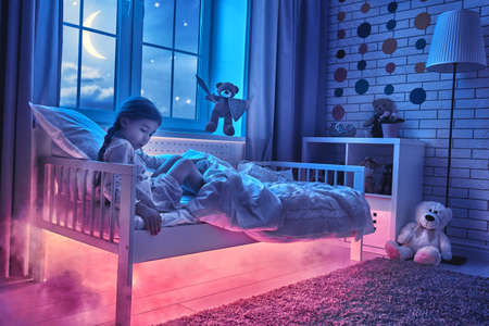 Photo for Nightmare for children. Little child girl is afraid of monsters in the dark of night. Frightened little girl and her teddy bear friend are protected against monsters. - Royalty Free Image