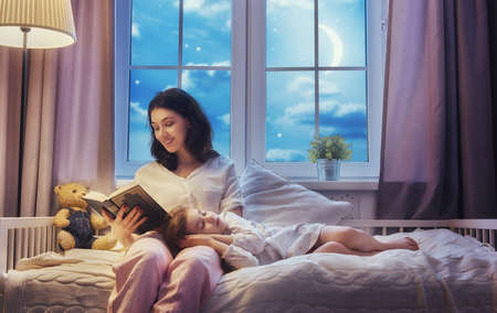 Photo pour Family reading bedtime. Pretty young mother reading a book to her daughter. - image libre de droit