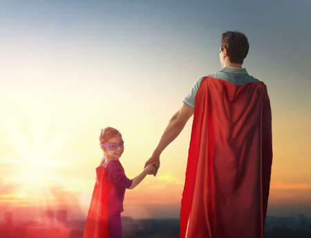 Foto de Happy loving family. Father and his daughter child girl playing outdoors. Daddy and his child girl in an Superhero's costumes. Concept of Father's day. - Imagen libre de derechos