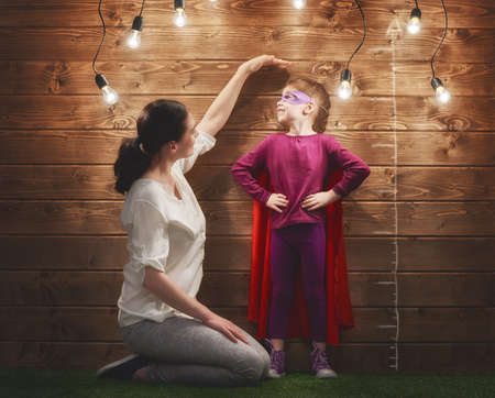 Photo for Mother measures the growth of her child daughter at a wooden wall. - Royalty Free Image