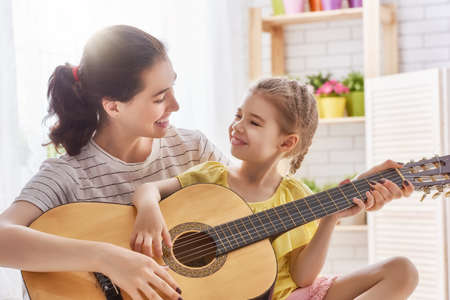 Foto de Happy family. Mother and daughter playing guitar together. Adult woman playing guitar for child girl. - Imagen libre de derechos