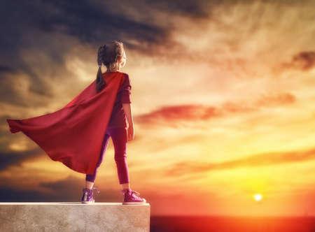 Foto de Little child plays superhero. Kid on the background of sunset sky. Girl power concept - Imagen libre de derechos