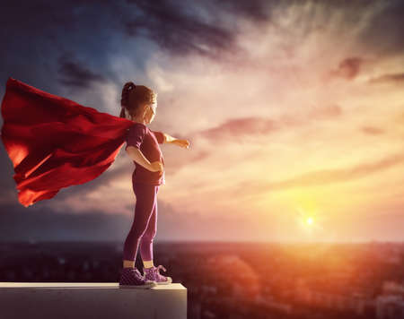 Photo pour Little child plays superhero. Kid on the background of sunset sky. Girl power concept - image libre de droit