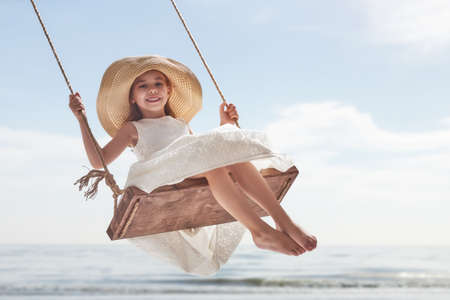 Photo for Happy laughing child girl on swing in summer day - Royalty Free Image