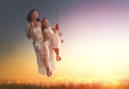 Photo for Happy loving family! Young mother and her child daughter swinging on the swings and laughing a summer evening outdoors. - Royalty Free Image