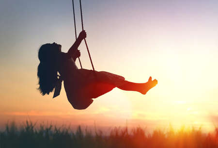 Photo for Happy laughing child girl on swing in sunset summer - Royalty Free Image
