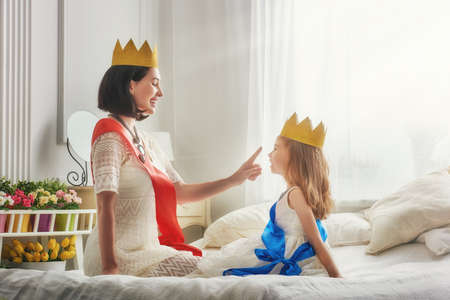 Photo pour Happy loving family is preparing for a costume party. Mother and her child girl playing together. Beautiful queen and princess in gold crowns. - image libre de droit